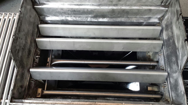 This photo shows the firebox back on the grill frame, with burner tubes, igniters, and stainless steel Flavorizer bars going back into the firebox.