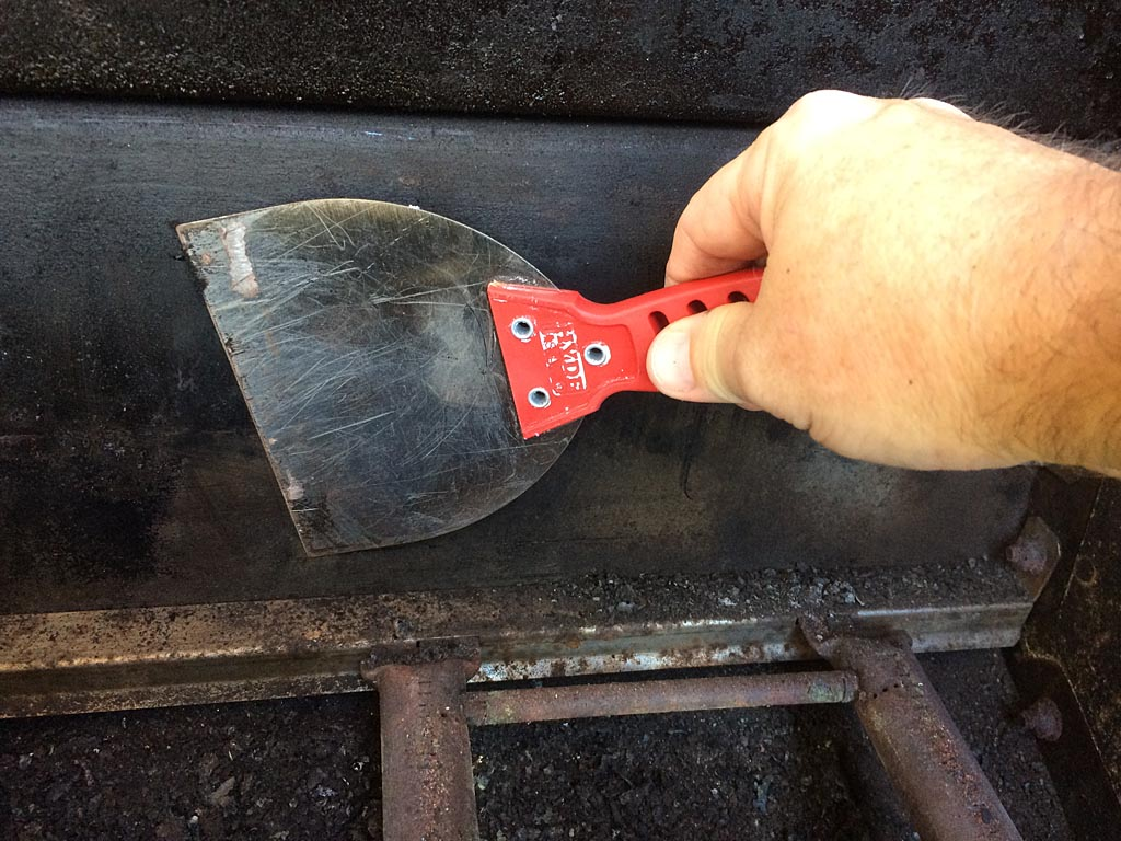 Scraping the upper part of the firebox with a wide putty knife