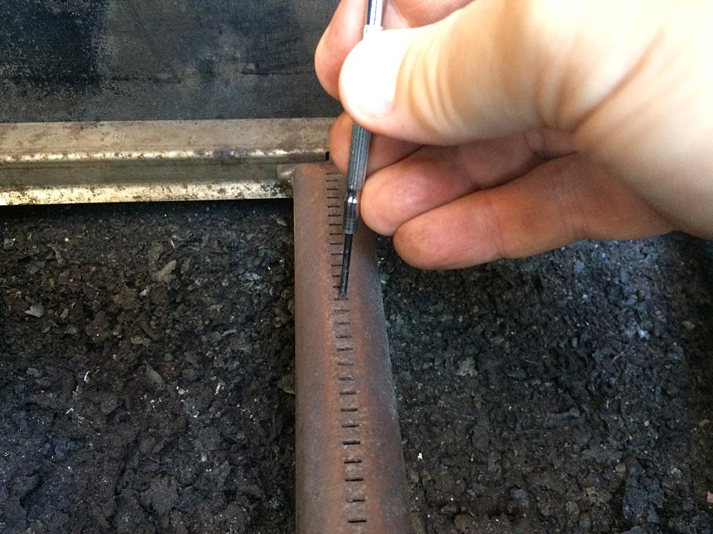 Punching-out clogged burner holes with an eyeglass screwdriver