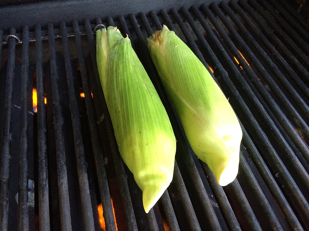 Fresh corn goes onto the grill