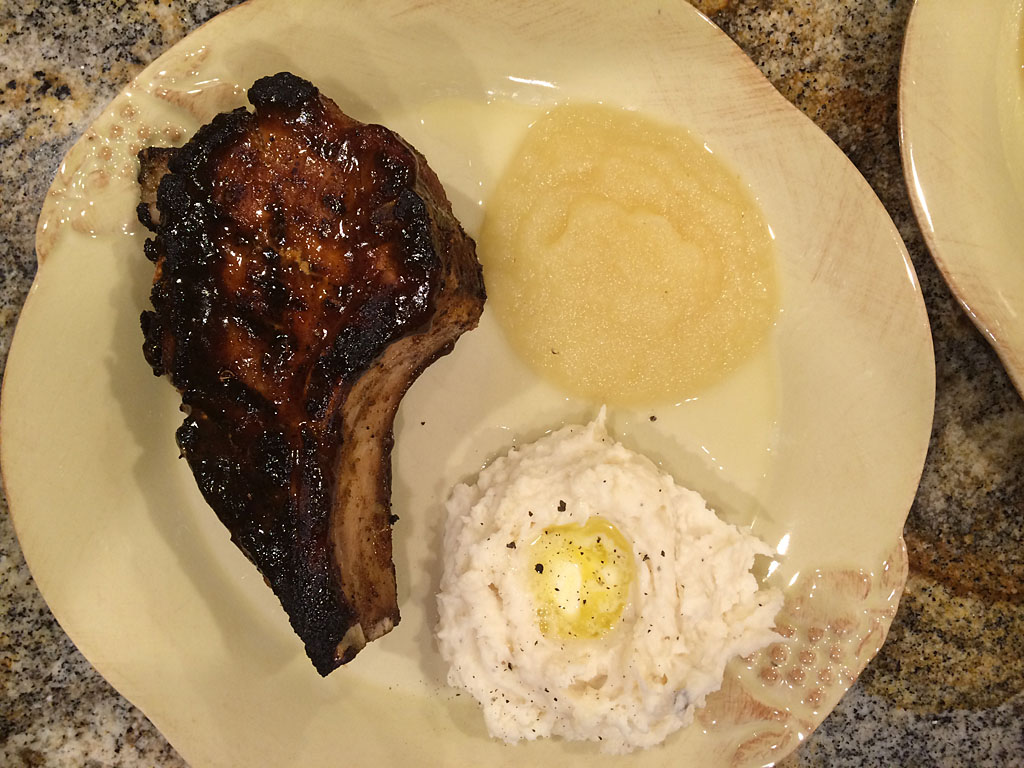 Plated pork chop with mashed potatoes and apple sauce
