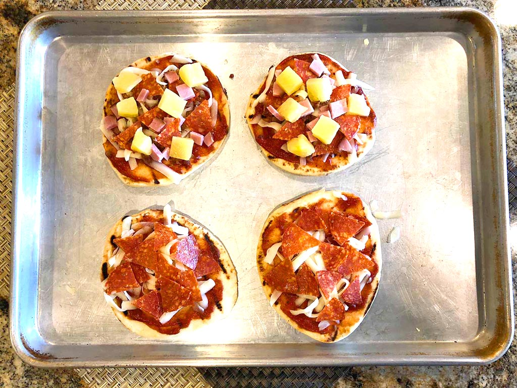 Adding sauce and toppings to naan