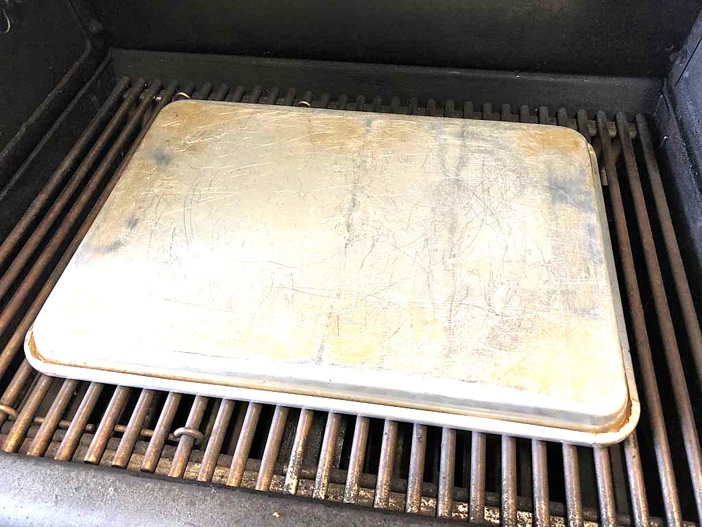 Placing baking sheet over naan to accelerate heating