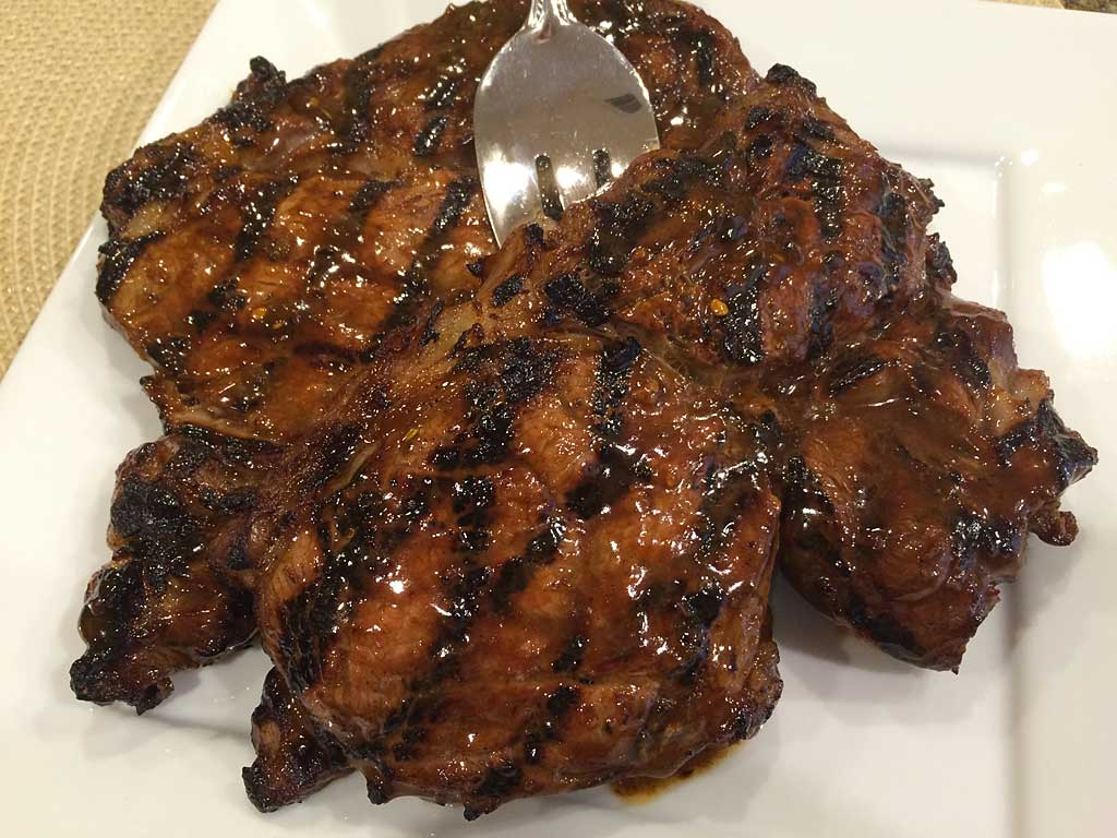 Caribbean Jerk marinated ribeye steaks on a serving platter