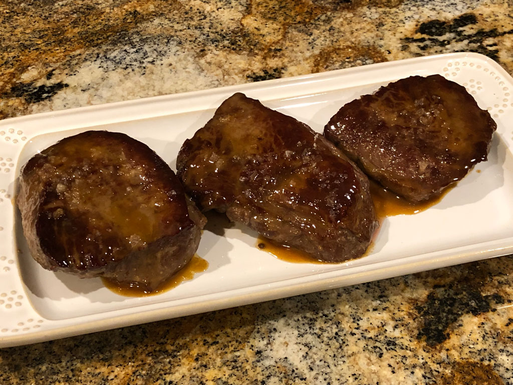 Finished sirloin steaks with pomegranate molasses glaze