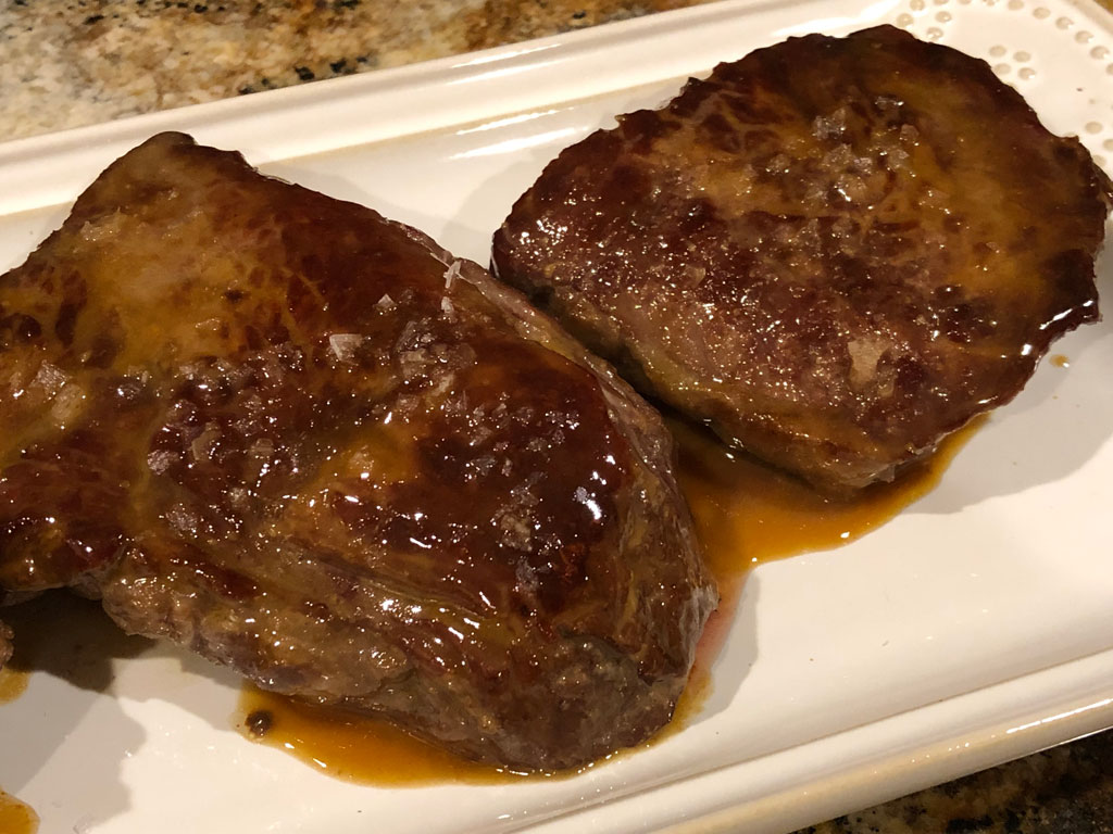 Close-up of sirloin steaks with pomegranate molasses glaze