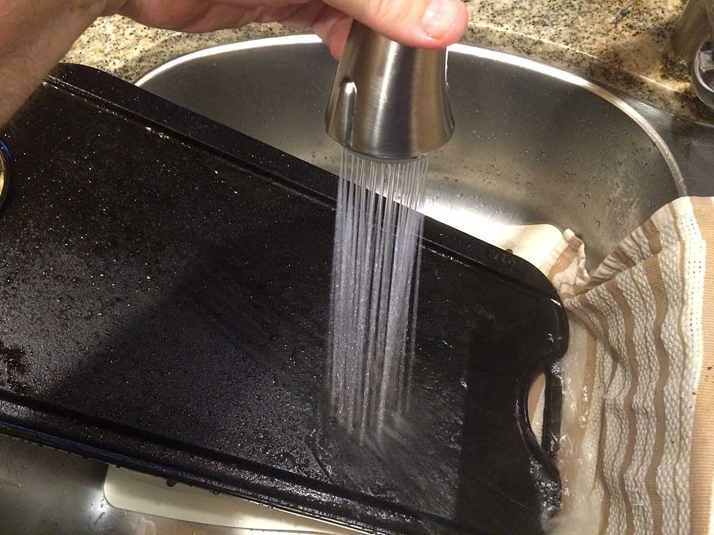 Rinsing cast iron griddle under very hot water.