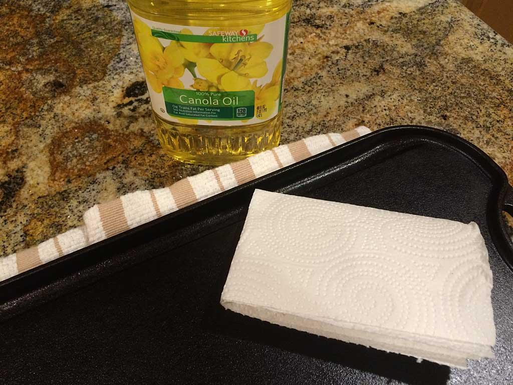 Applying a thin coat of canola oil to hot cast iron.