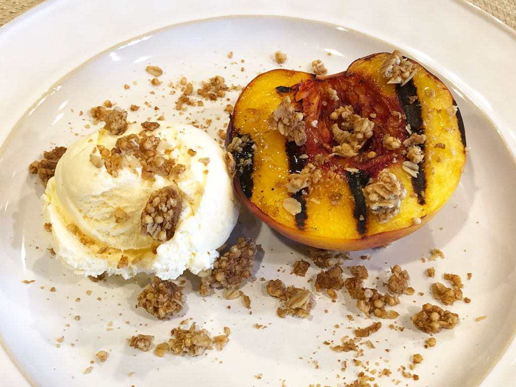 Finished grilled peach with ice cream and granola crumble